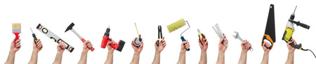 crowd hands: Hands raised holding different tools Stock Photo