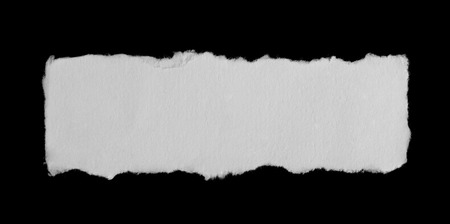 Piece of a paper isolated on black Foto de archivo