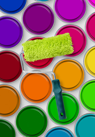 tins: Paint roller on paint tins Stock Photo