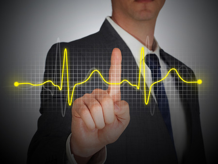 taking pulse: Businessman touch Heart rate digital screen Stock Photo