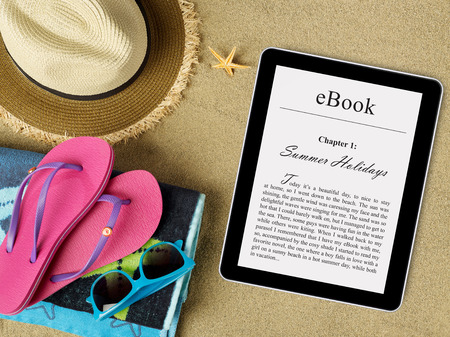 eBook tablet on beach Imagens