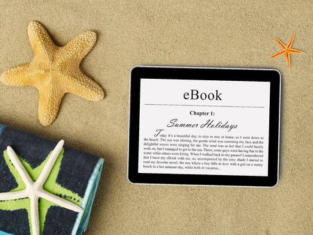 eBook tablet on beach Фото со стока