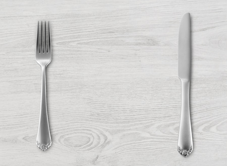 Table knife and fork on wood