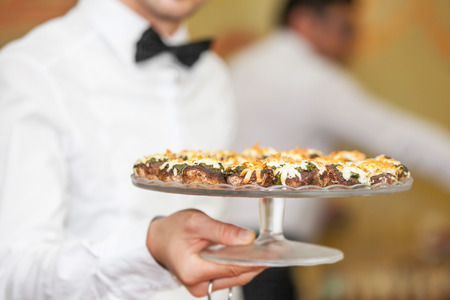 servings: Waiter serving stuffed mushrooms