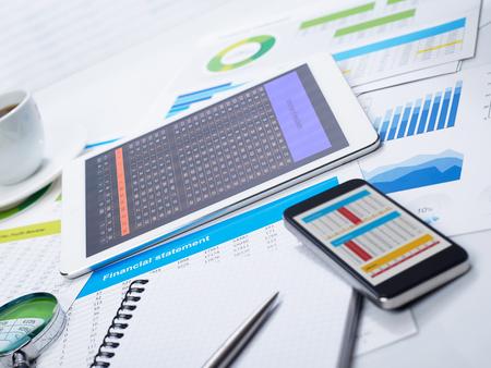 documentos: Tablet en los papeles del escritorio y financieros Foto de archivo