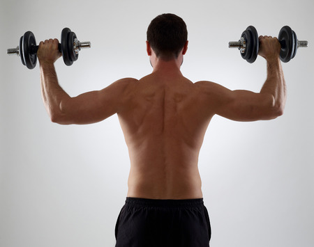 muscle training: Muskulöser Mann mit Gewichten, isoliert auf grau