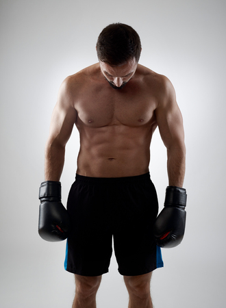 pressure loss: Defeated boxer looking down, gray background