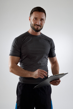 sportsmen: Coach with clipboard looking at camera Stock Photo