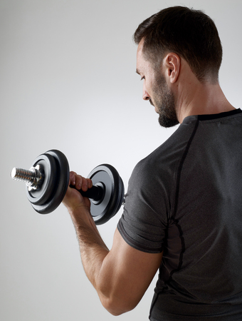 arm up: Muscular man with weights, isolated on gray