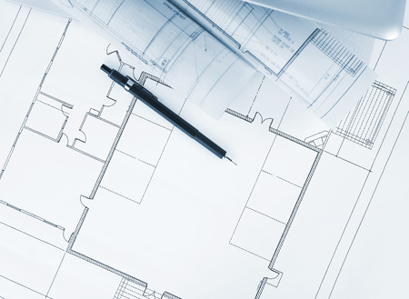 housing problems: Blueprints and laptop Stock Photo