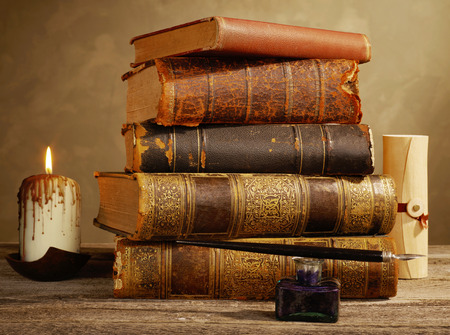 Tintenfass, Feder, Kerzen und antike Bücher Standard-Bild
