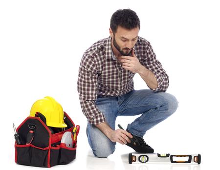 Handyman with toolbelt measuring on floor Stock Photo