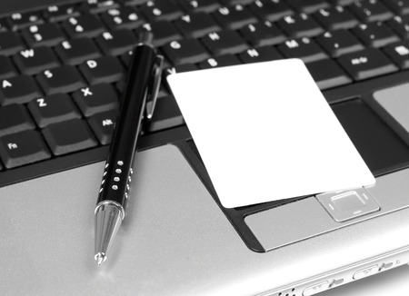 Business card and pen on laptop Stock Photo