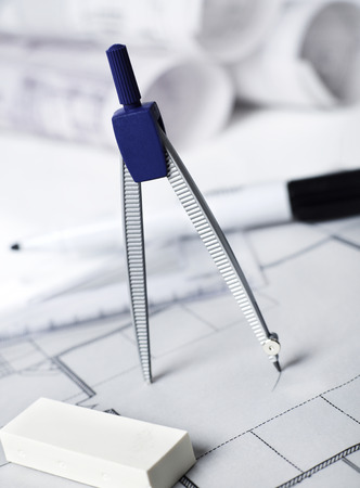 Drawing compass on blueprints Stock Photo