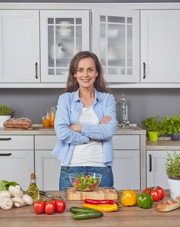 Cheerful woman in the kitchen Imagens