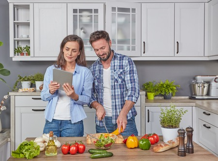 Young couple cooking a recipe from a digital tablet Imagens