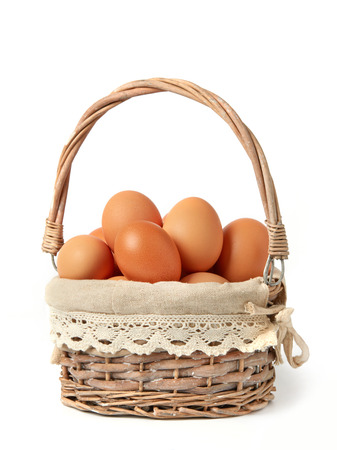 Rustic eggs in a basket on white