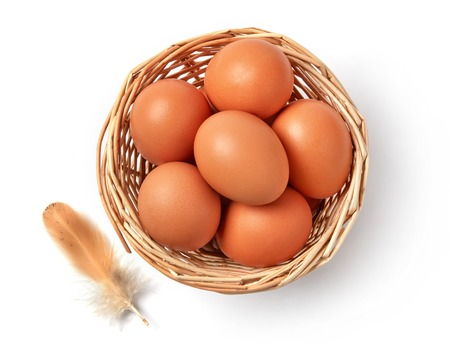 Farm eggs in a basket isolated on white