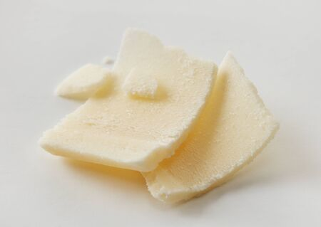 Parmesan flakes close-up on gray