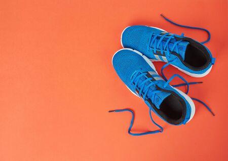 Blue sport shoes on orange background Stock fotó
