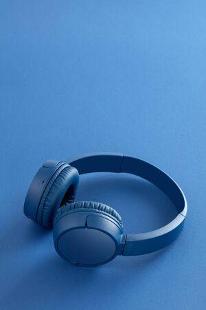 Blue wireless headphones on blue background Foto de archivo