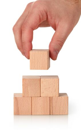Closeup of businessman making a wooden blocks pyramid