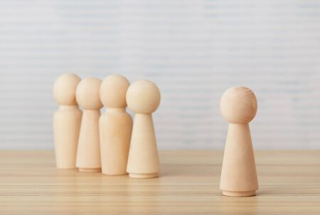Follow the leader concept with wooden figurines