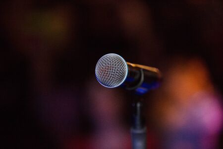 Vocal microphone on a stage at night, copy space