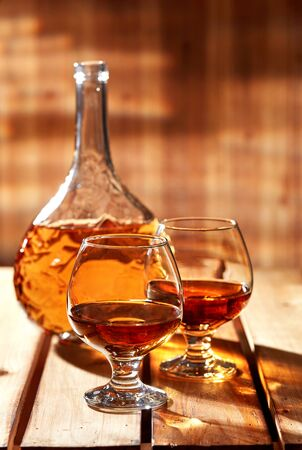 Glasses and bottle of brandy on old wooden table