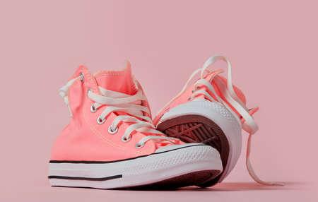 Pink canvas shoes on pink background Standard-Bild