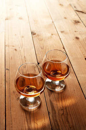Glasses of cognac on old wooden table