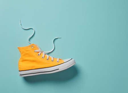 Yellow canvas shoe on blue background