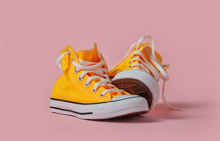 Yellow canvas shoes on pink background
