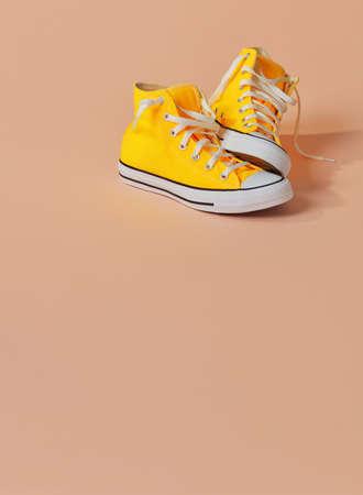 Yellow canvas shoes on orange background