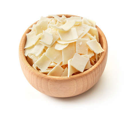 Parmesan flakes in a wooden bowl on white background