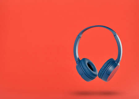 Wireless blue headphones on red background