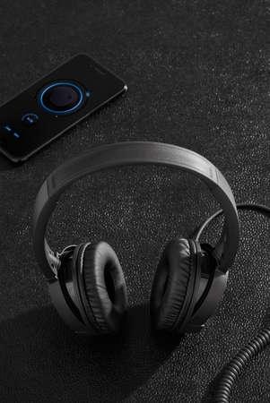 Black headphones and mobile phone on black