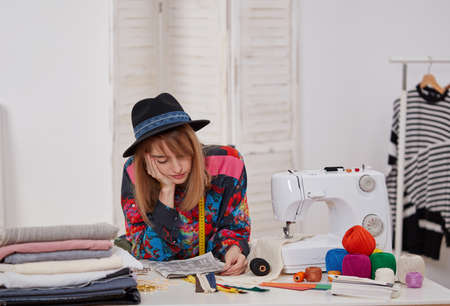Young fashion designer thinking at the worktable Banque d'images