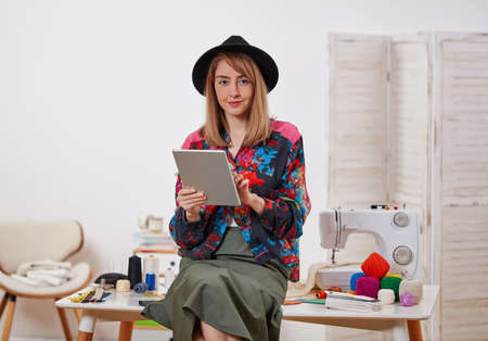 Fashion designer with digital tablet and sewing machine