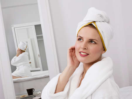 Young woman in white towel wrapped around head and robe