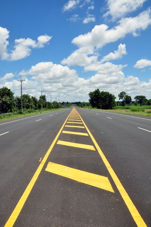 yellow line traffic symbol with asphalt street in blue sky Stock Photo