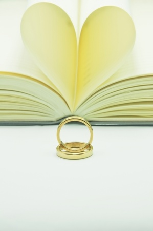 Two ring sit on book heart photo