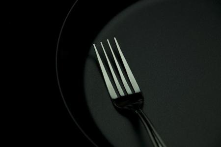 fork in black disk as black background photo