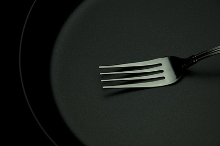 White fork push on black disk as black background photo