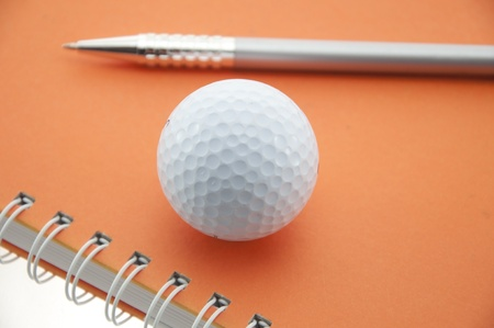 golf ball and pen push on orange color notebook photo