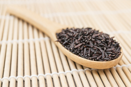 close up Black organic rice put on wooden spoon as bamboo background view photo