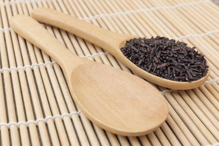close up Black organic rice put on wooden spoon compare with empty wooden spoon as bamboo background view photo