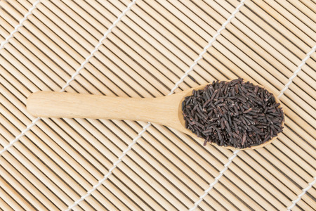 Black organic rice on wooden spoon as bamboo wooden background