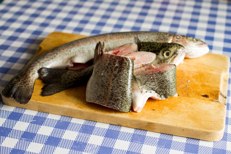 rearing of fish: Chopped trouts on wooden cutting board Stock Photo