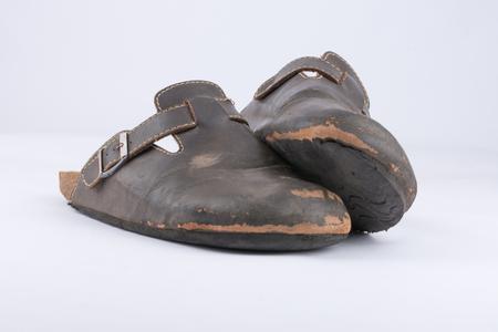 ortopedia: Zapatillas de cuero viejas que son muy usadas
